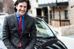 Handsome corporate man posing in front of his new car Royalty Free Stock Image