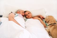 Handsome couple in bed sleeps together in association with dog. Handsome couple in bed sleeps together in association with their dog. A yellow labrador Stock Photo