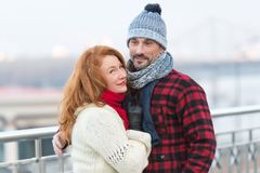 Handsome couple likes walking in city. Aged guy and woman likes winter. Rude woman cuddles to guy in red jacket. Man and woman. stock image