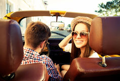 Handsome couple looking at camera sitting in car, view from rear seat royalty free stock photography