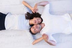 Handsome couple lying on floor Stock Photography