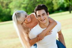 Handsome couple piggybacking in park. Royalty Free Stock Photos