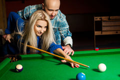 Handsome couple plays billiard on the pool table Stock Photos