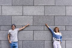 Handsome couple is pointing away and smiling, standing against gray wall. royalty free stock image