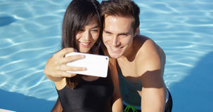 Handsome couple take photo while standing in pool Royalty Free Stock Photo