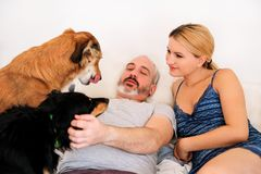 Handsome couple with their dogs on bed in morning. Young men and women spending time with their pets in bedroom. Happiness couple enjoying with their dogs at Royalty Free Stock Photography