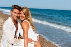 Handsome couple in white on beach. Stock Images