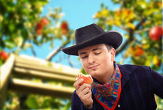 Handsome cowboy eating red apple Royalty Free Stock Photos