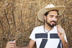 Handsome cowboy holding a pitch fork in stable Stock Photo