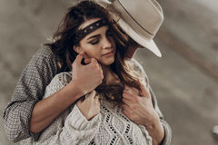 Handsome cowboy man in white hat touching cheek of beautiful boh. Handsome cowboy men in white hat touching cheek of beautiful boho gypsy women with leather stock image