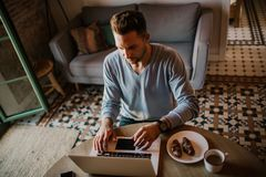 Handsome coworker man working at living room at home. Man sitting at wooden table using laptop and mobile phone. Blurred. Background stock image