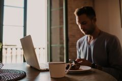 Handsome coworker man working at living room at home. Man sitting at wooden table using laptop and mobile phone. Blurred. Background royalty free stock photos
