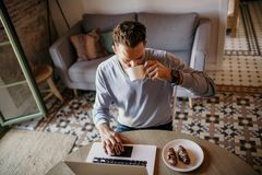 Handsome coworker man working at living room at home. Man sitting at wooden table using laptop and mobile phone. Blurred. Background stock photo