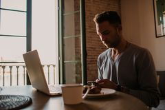 Handsome coworker man working at living room at home. Man sitting at wooden table using laptop and mobile phone. Blurred. Background stock photos