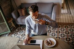 Handsome coworker man working at living room at home. Man sitting at wooden table using laptop and mobile phone. Blurred. Background stock photography