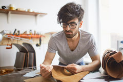 Handsome Craftsman Working with Leather in Studio Stock Photo