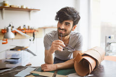 Handsome Craftsman in Workshop. Portrait of handsome middle eastern man wearing creative haircut looking away and smiling, leaning on workshop table while Royalty Free Stock Photos