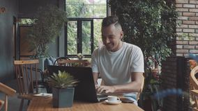 Handsome crazy emotional young happy male guy businessman shows success in cosy cafe. Man work on compter, smiling in. Front of laptop. Male made perfect sale stock video