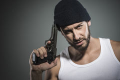 Handsome criminal holding a gun Stock Photo