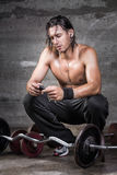 Handsome crouched athlete. Portrait of handsome crouched athlete checking his music player while having a rest from workout Royalty Free Stock Image