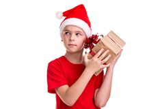 Handsome curious boy, santa hat on his head, checking the gift box. Concept: christmas or Happy New Year holiday royalty free stock images