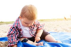 Handsome curious child sitting on sand on the beach playing Stock Images