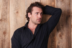 Handsome curly man in black shirt with hand behind head Stock Photo