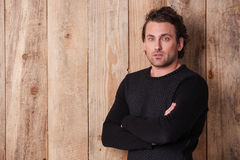 Handsome curly man in black sweater standing with arms crossed Royalty Free Stock Image