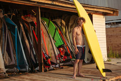 Handsome curly man surfer standing and holding yellow surfing board. Full length of handsome curly man surfer standing and holding yellow surfing board Stock Photography