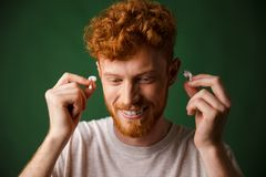 Handsome curly redhead man in white t-shirt insert earphones in. His ears, over green background Stock Photos