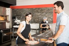 Smiling chef woman preparing pizza for customer standing behind royalty free stock photo