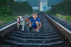 Handsome cute boy in blue shirt together with slobbery english bull dog standing on rail ways.Two friends boy and dog Royalty Free Stock Images