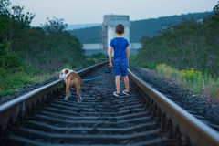 Handsome cute boy in blue shirt together with slobbery english bull dog standing on rail ways.Two friends boy and dog Royalty Free Stock Photo