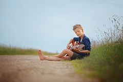Handsome cute boy is playing on acoustic guitar sittingon road in summer day. Stock Photo