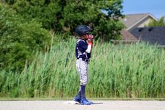 Handsome cute Young boy playing baseball waiting and protecting the base. Stock Photography