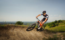 Handsome cyclist rides bike in the mountains Stock Images