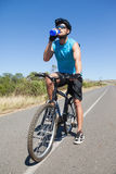 Handsome cyclist taking a break on his bike drinking water Royalty Free Stock Image