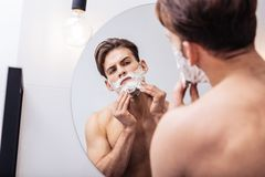 Handsome dark-eyed man wearing no shirt using shaving foam. Wearing no shirt. Handsome dark-eyed man wearing no shirt using shaving foam before going to work royalty free stock photography