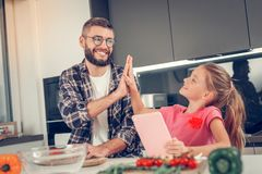 Handsome dark-haired bearded man in a checkered shirt looking amused. Farther and daughter. Handsome dark-haired bearded men wearing a checkered shirt looking stock photography
