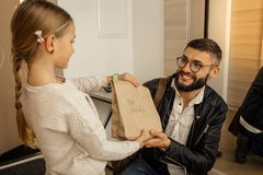 Handsome dark-haired bearded man in eyewear feeling amused. Pleased. Handsome dark-haired bearded men in eyewear feeling amused while receiving a present from royalty free stock photo