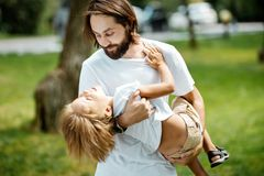 Handsome dark-haired father with beard dressed in the white t-shirt is holding in the arms his little son and watching stock photo