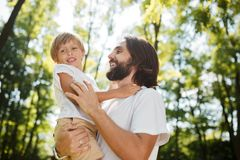 Handsome dark-haired father with beard dressed in the white t-shirt is holding in the arms his little son and watching royalty free stock photography