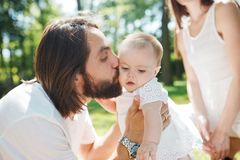 Handsome dark-haired father with beard is kissing his little charming daughter on a summer day in the park. stock photo