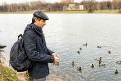 Handsome dark-haired middle-aged man in jacket, cap and backpack. Feeds ducks on pond in city park in late autumn. Authentic lifestyle moments royalty free stock photos