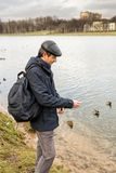 Handsome dark-haired middle-aged man in jacket, cap and backpack. Feeds ducks on pond in city park in late autumn. Authentic lifestyle moments royalty free stock photography