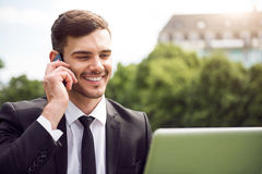 Handsome delighted man sitting on the grass. Pleasant interlocutor. Cheerful delighted smiling man using laptop and talking on cell phone while resting outdoor Royalty Free Stock Photo