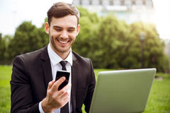Handsome delighted man sitting on the grass. Share positivity. Cheerful content smiling man holding cell phone and using laptop while sitting on the grass Royalty Free Stock Photos