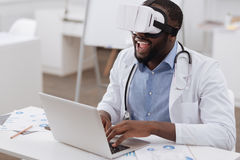 Handsome delighted man using a laptop. Scientific research. Handsome pleasant delighted man sitting at the laptop and typing while wearing virtual reality Stock Image