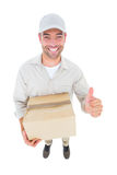 Handsome delivery man with cardboard box gesturing thumbs up Royalty Free Stock Photography