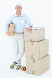 Handsome delivery man leaning on stacked cardboard boxes Stock Photos